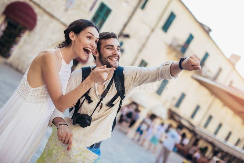 Pares de sorriso de turistas nos óculos de sol com o mapa na cidade fotos de stock royalty free