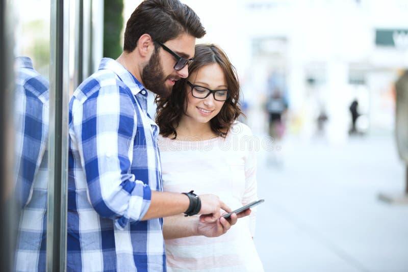 Pares de sorriso usando o telefone esperto junto na cidade fotografia de stock royalty free