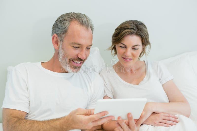 Pares de sorriso usando a tabuleta digital na cama no quarto fotografia de stock royalty free