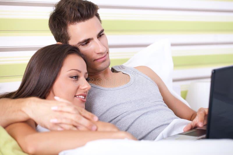 Pares de sorriso usando um portátil que encontra-se em sua cama imagem de stock royalty free