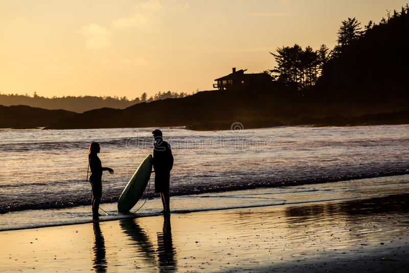 Pares de surfistas na praia de Tofino no por do sol imagens de stock royalty free