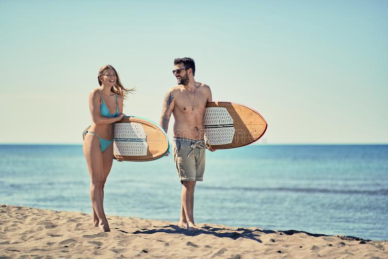 Pares de surfistas que andam no estilo de vida exterior do verão da praia fotografia de stock