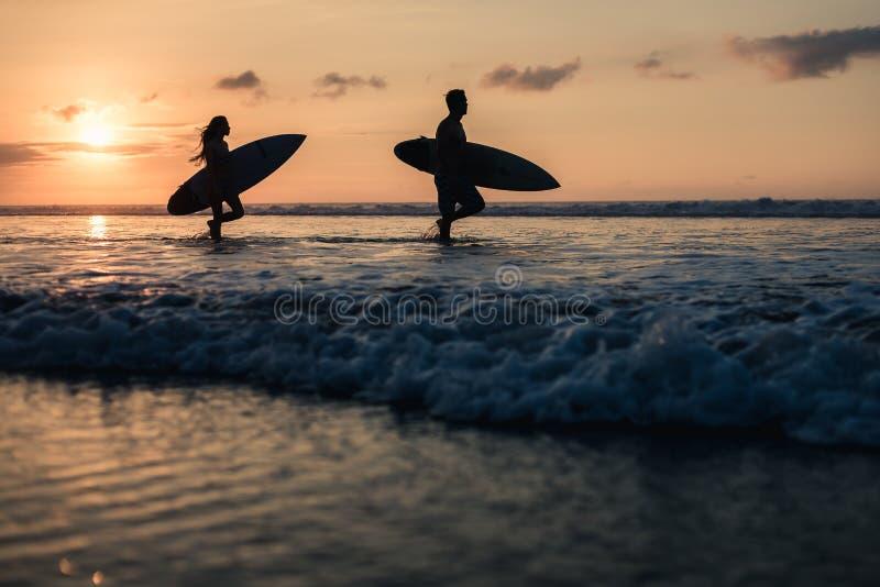 Pares de surfistas sobre o por do sol no litoral foto de stock