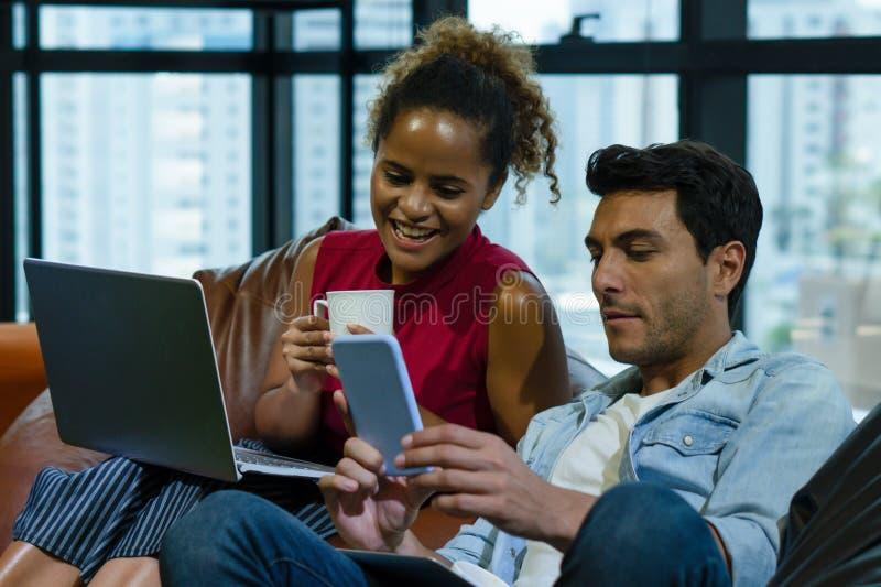 Pares de trabajo felices con el trabajo junto en oficina con el ordenador imágenes de archivo libres de regalías