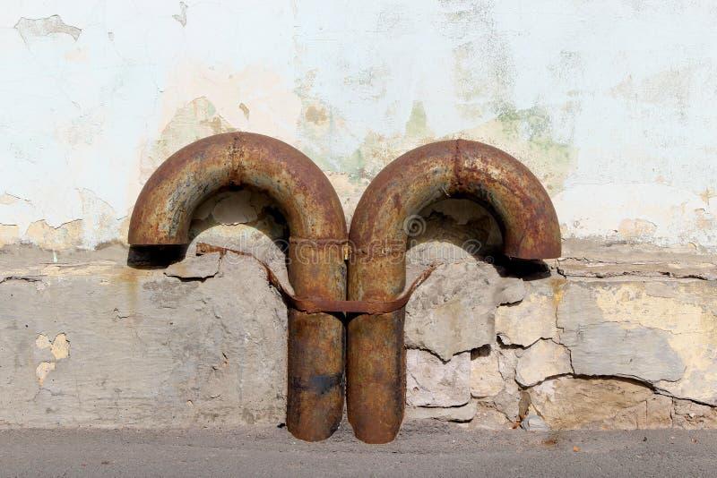 Pares de tubulações oxidadas da ventilação do vintage do metal curvado na parede coberta no emplastro danificado velho imagens de stock