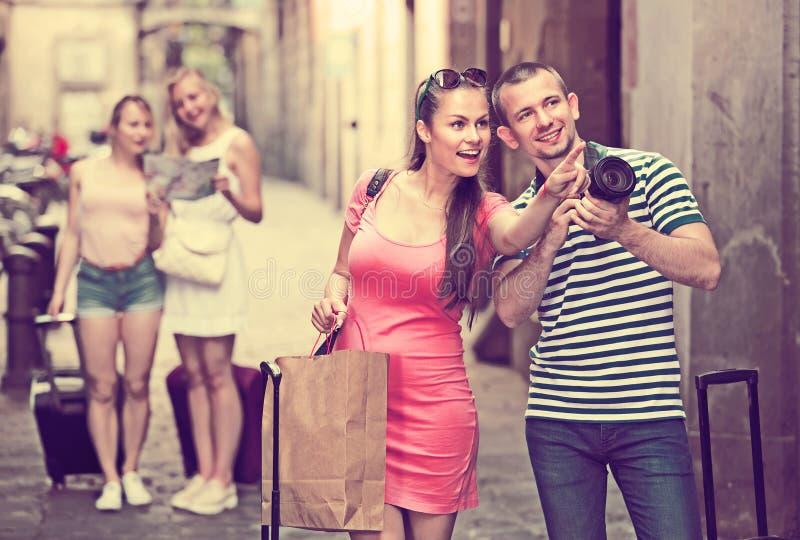 Pares de turistas de sorriso que guardam a câmera nas mãos imagens de stock