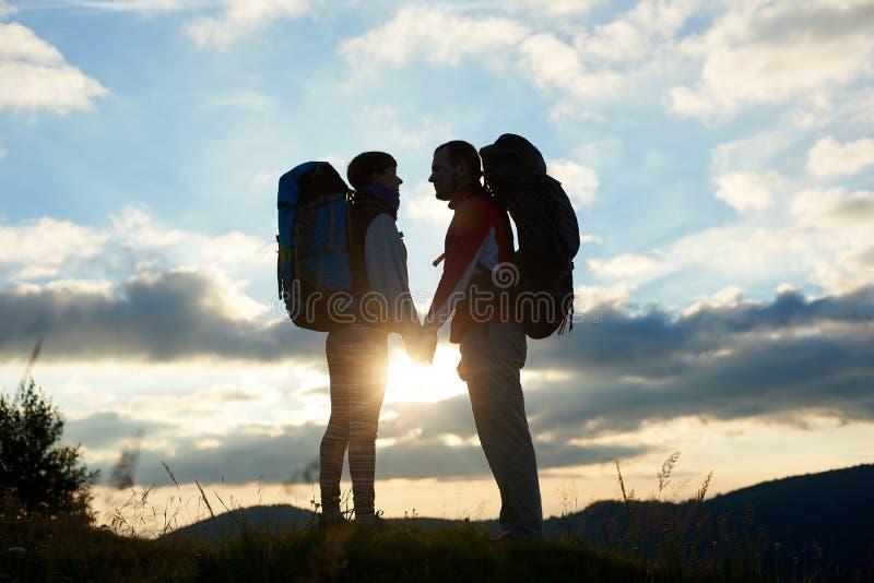 Pares de turistas en amor con las mochilas que se hacen frente en la puesta del sol en las montañas fotos de archivo libres de regalías