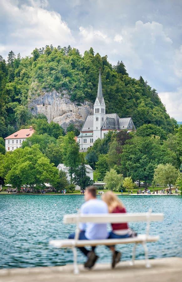 Pares de turistas novos no amor Apreciar a vista panorâmica do lago sangrou, localizado em Eslovênia, Europa foto de stock
