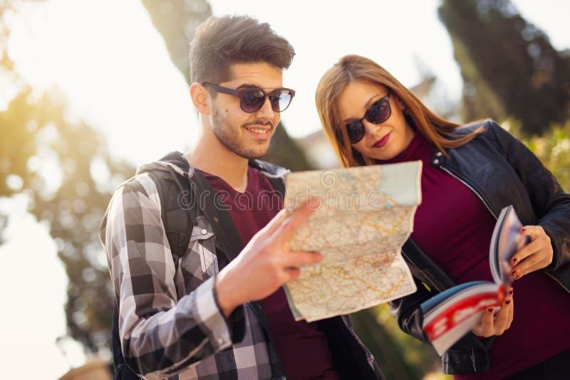 Pares de turistas que olham o guia e um mapa do viajante foto de stock royalty free