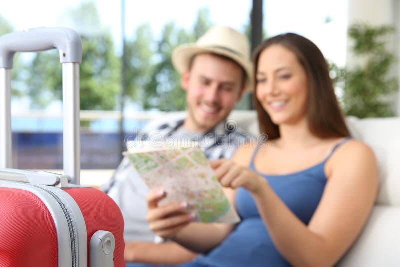 Pares de turistas que procuram o lugar em um mapa imagem de stock royalty free