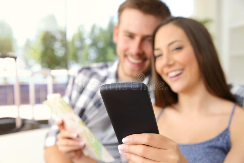 Pares de turistas que procuram o lugar em um telefone imagens de stock