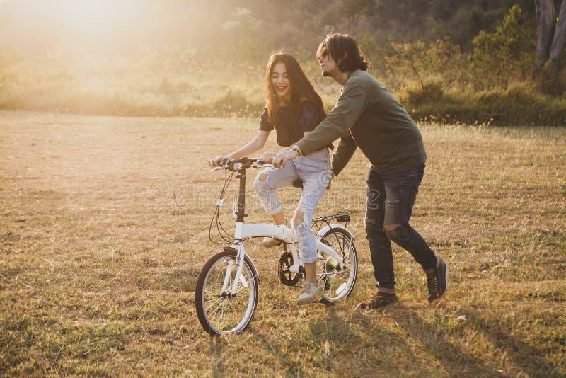 Pares de un hombre más joven y de la mujer asiáticos que se relajan en patio AG foto de archivo