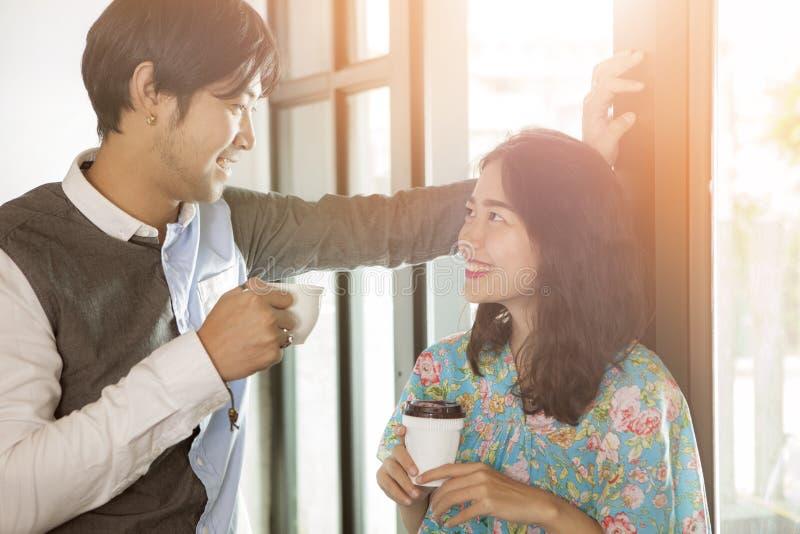Pares de un hombre y de una mujer asiáticos más jovenes con la taza de café t disponible imagen de archivo