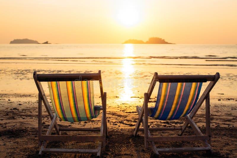 Pares de vadios da praia no por do sol do mar imagens de stock royalty free