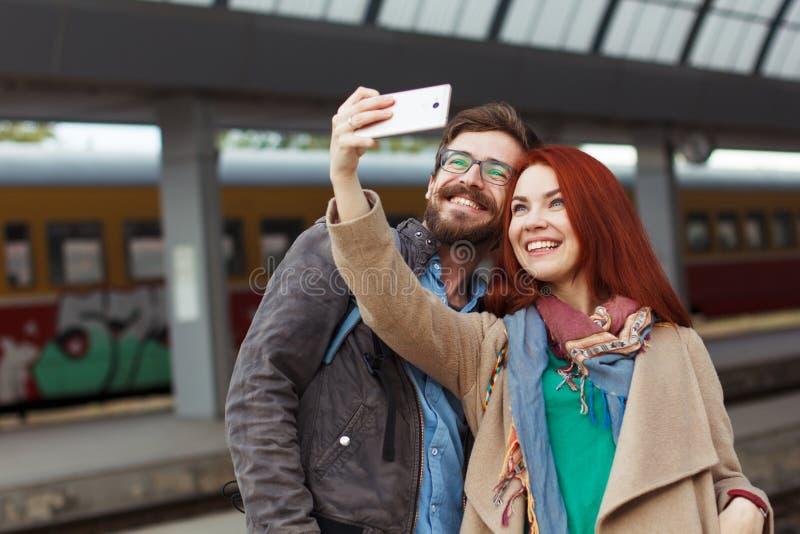 Pares de viajantes do moderno que fotografam um selfie com um smartphone em um estação de caminhos-de-ferro conceito do curso móv imagem de stock