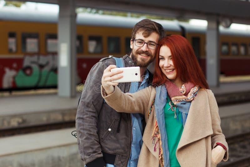 Pares de viajantes do moderno que fotografam um selfie com um smartphone em um estação de caminhos-de-ferro conceito do curso móv imagem de stock royalty free
