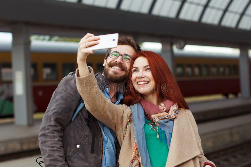 Pares de viajantes do moderno que fotografam um selfie com um smartphone em um estação de caminhos-de-ferro conceito do curso móv fotografia de stock