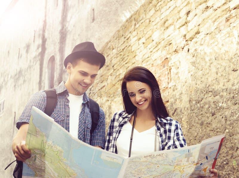 Pares de viajantes novos com mapa: passeio em torno da cidade fotografia de stock