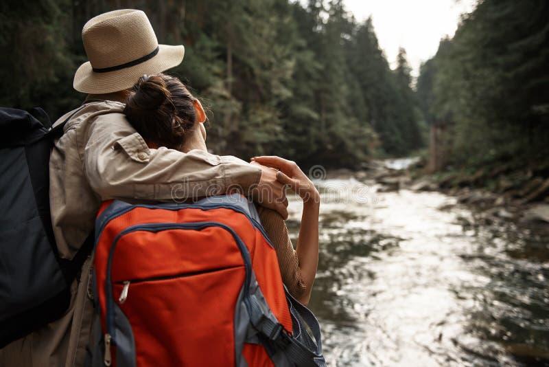 Pares de viajantes que abraçam e que olham o fluxo das árvores e do rio foto de stock