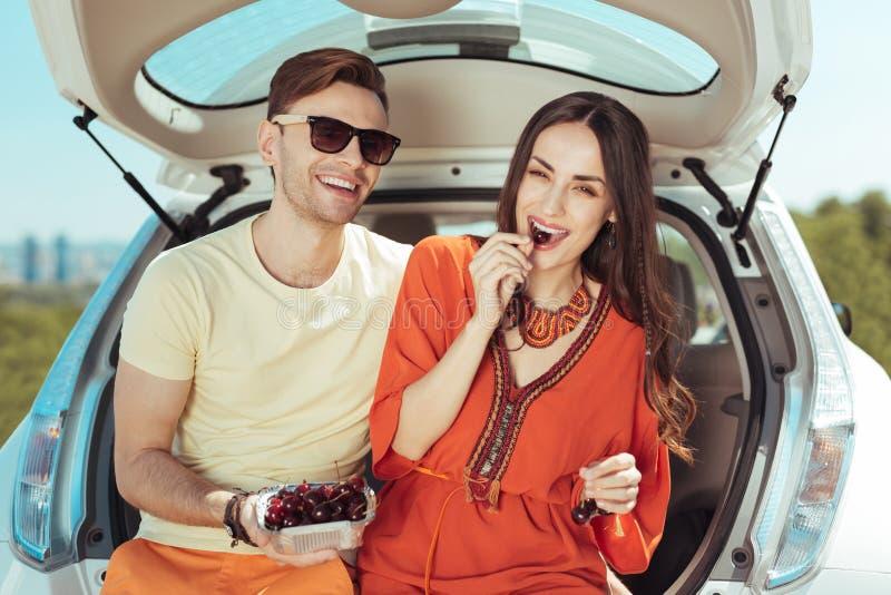 Pares de viajantes que sentam-se no tronco de seu carro que come cerejas doces imagens de stock royalty free