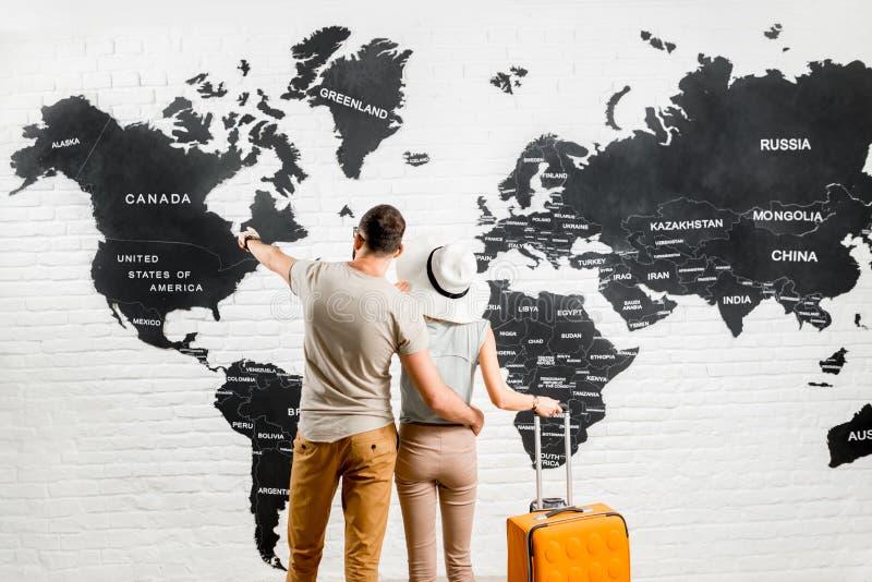 Pares de viajeros cerca del mapa del mundo fotografía de archivo
