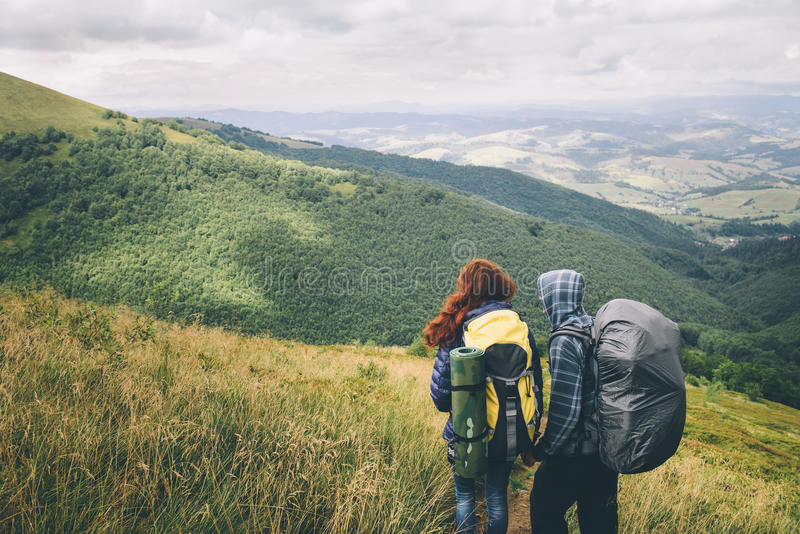 Pares de viajeros con las mochilas que miran en las colinas imágenes de archivo libres de regalías