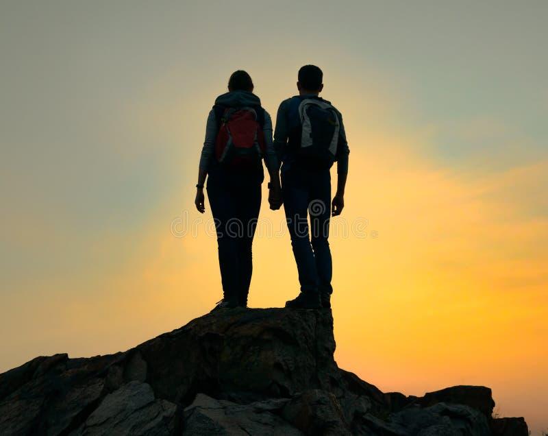 Pares de viajeros jovenes con la mochila que se coloca en el top de la roca en la puesta del sol del verano Concepto del viaje y  imagen de archivo libre de regalías