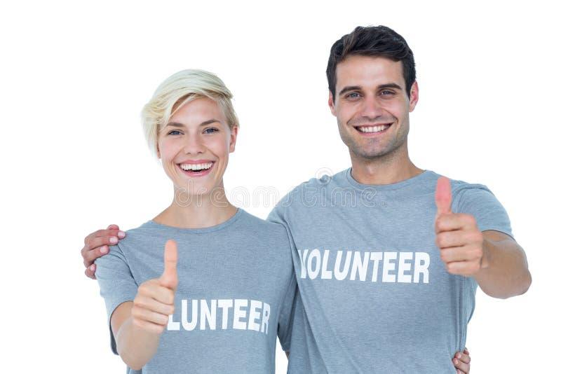 Pares de voluntários dos jovens que gesticulam os polegares acima imagens de stock royalty free