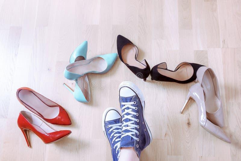 Pares de zapatilla de deporte rodeados por los zapatos elegantes imagen de archivo