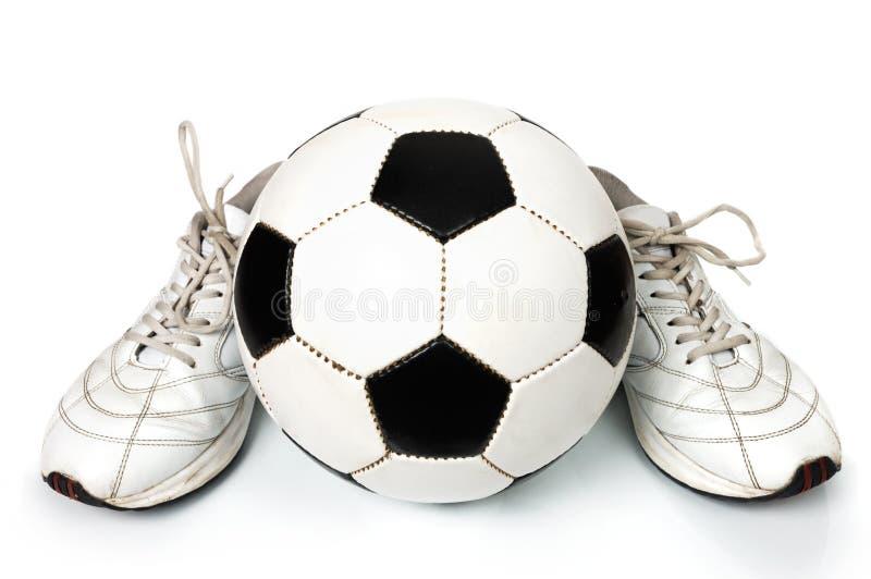 Pares de zapatillas de deporte y de balón de fútbol fotografía de archivo libre de regalías