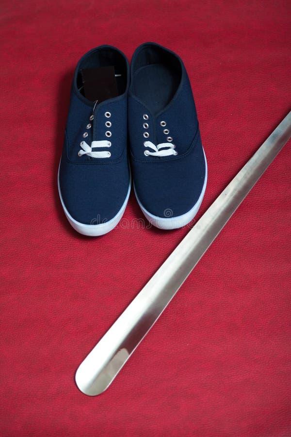 Pares de zapatillas de deporte y de cuerno azules del zapato en fondo rojo imagenes de archivo