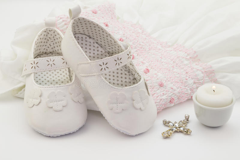 Pares de zapatos de bebé blancos en el vestido blanco bordado del bautizo, imagen de archivo libre de regalías