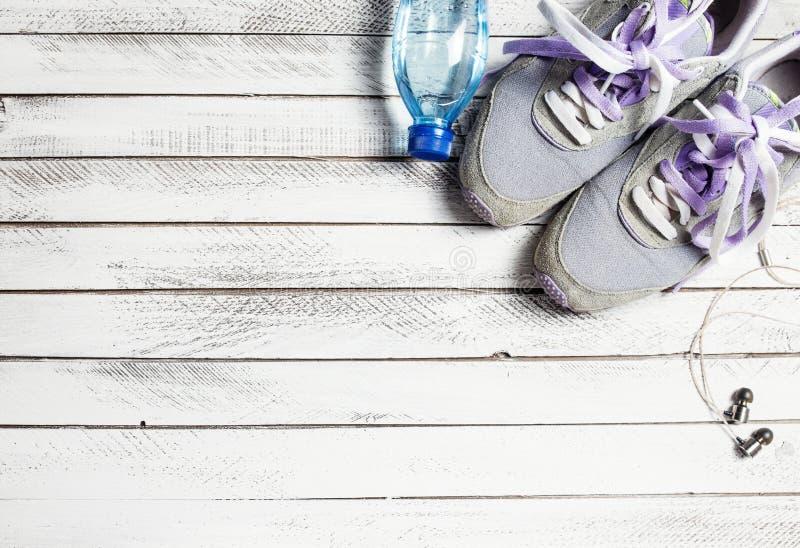 Pares de zapatos, de botella de agua y de auriculares del deporte en la madera blanca fotos de archivo
