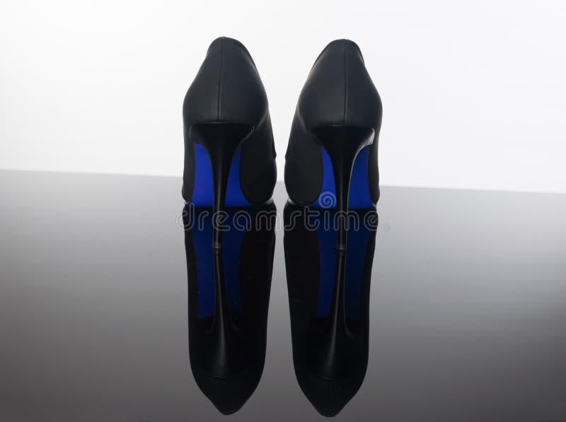 pares de zapatos de la mujer acentuada con los tacones altos negros del azul de los lenguados fotografía de archivo libre de regalías
