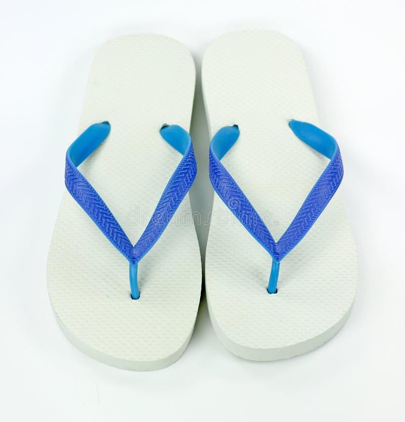 Pares de zapatos de las chancletas en el fondo blanco foto de archivo