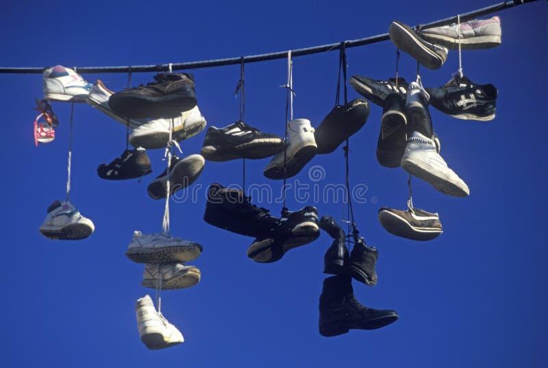 Pares de zapatos múltiples arrojados sobre el alambre eléctrico por los cordones imagen de archivo libre de regalías