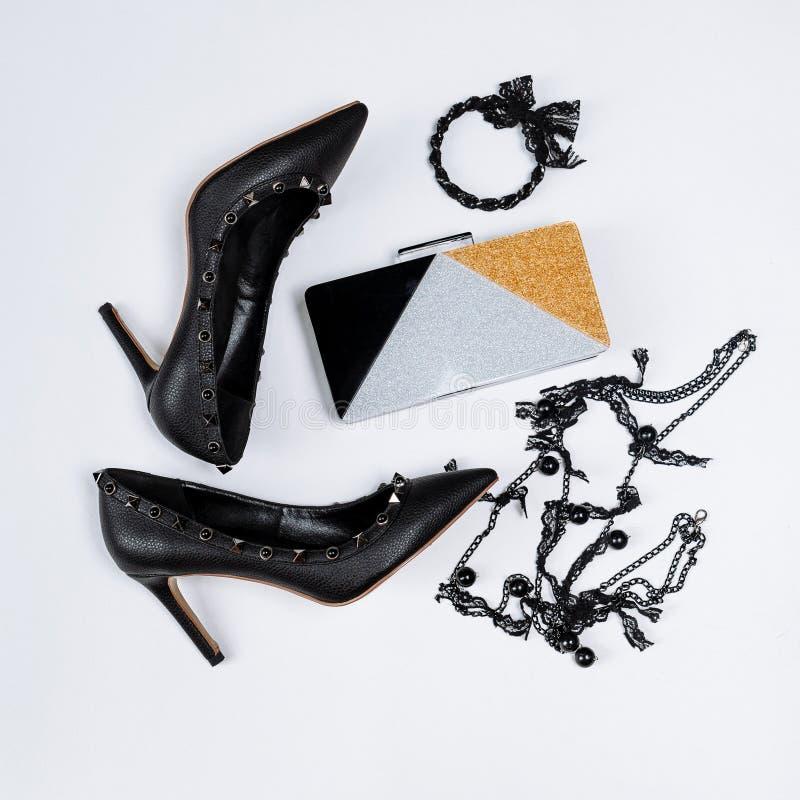 Pares de zapatos negros adornados con acentos del metal, joyería con el cordón y las gotas negros y un embrague tricolor con las  fotografía de archivo libre de regalías