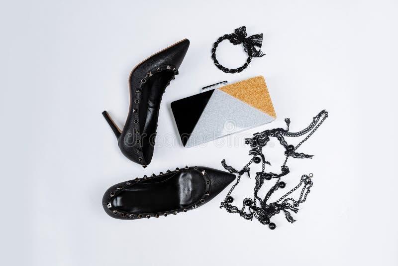 Pares de zapatos negros adornados con acentos del metal, joyer?a con el cord?n y las gotas negros y un embrague tricolor con las  fotos de archivo