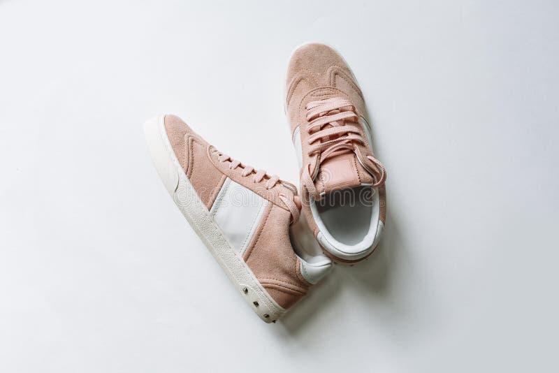 Pares de zapatos rosados del ante con los acentos blancos en un fondo blanco imagen de archivo libre de regalías