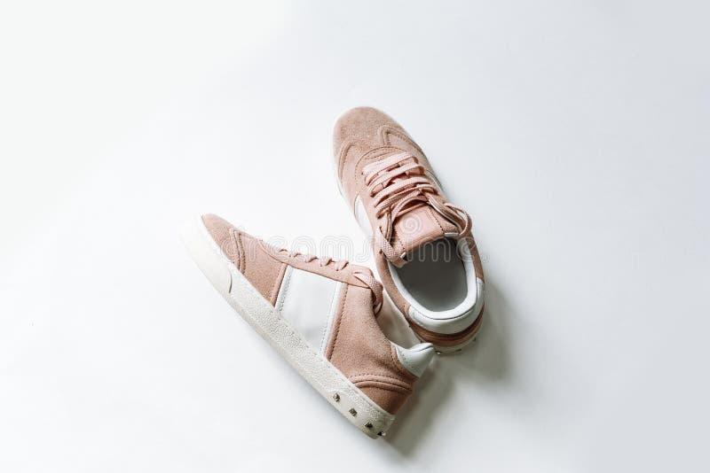 Pares de zapatos rosados del ante con los acentos blancos en un fondo blanco imagen de archivo