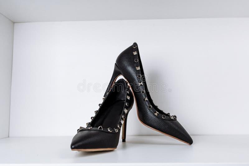 Pares de zapatos de tac?n alto negros con las puntas puntiagudas, adornados con los partes movibles del metal contra un estante e fotografía de archivo libre de regalías