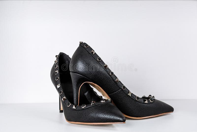 Pares de zapatos de tac?n alto negros con las puntas puntiagudas, adornados con los partes movibles del metal contra un estante e imagen de archivo