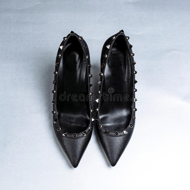 Pares de zapatos de tac?n alto negros con las puntas puntiagudas, adornados con los partes movibles del metal contra un estante e imagenes de archivo
