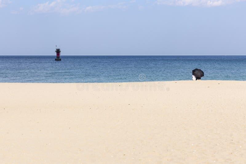 Pares debajo del paraguas en la playa imagen de archivo