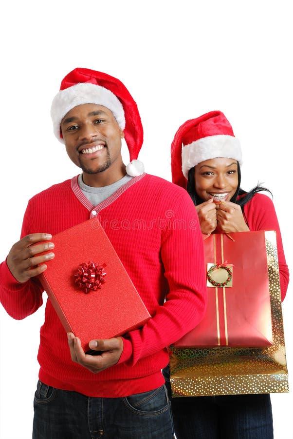 Pares del afroamericano con los regalos de la Navidad fotos de archivo