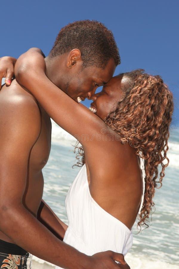 Pares del afroamericano en amor en la playa imagenes de archivo