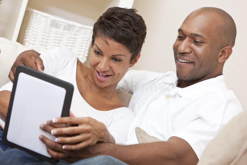 Pares del afroamericano usando el ordenador de la tablilla foto de archivo libre de regalías