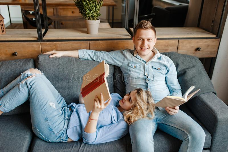 Pares del amor que descansan sobre el sofá cómodo en casa foto de archivo