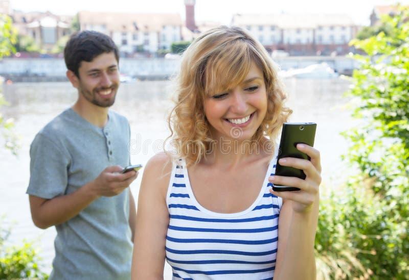 Pares del amor que envían el mensaje con el teléfono móvil imagenes de archivo