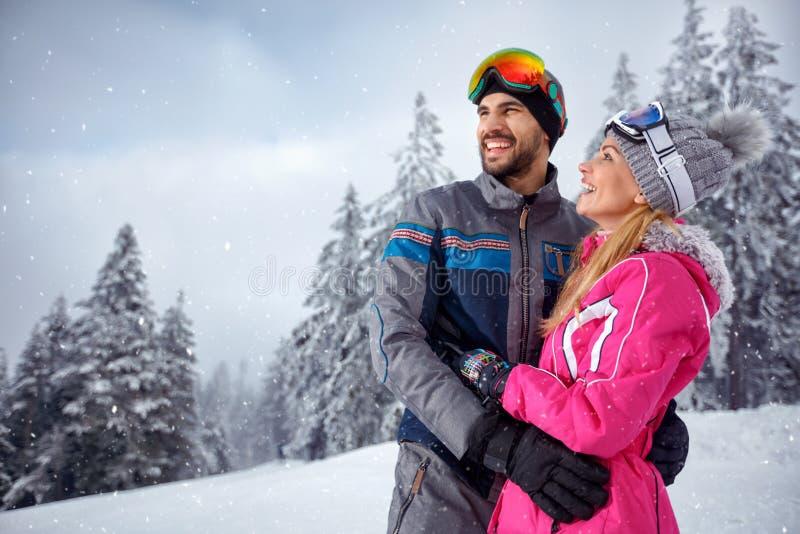 Pares del amor que gozan el vacaciones del invierno junto en la montaña imagen de archivo